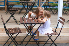 Little happy girls have fun at outdoor cafe Royalty Free Stock Images