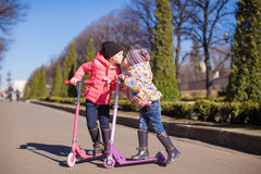 Little happy girls with scooter outdoors. Little adorable girls with scooter in spring park Stock Photo