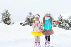 Little happy girls skating outdoors in winter snow Royalty Free Stock Photo