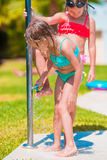 Little happy girls under beach shower on tropical beach Royalty Free Stock Image