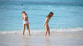 Little happy kids have a lot of fun at tropical beach playing together. Little girls having fun at tropical beach playing together at shallow water. Adorable stock video