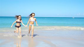 Little happy kids have a lot of fun at tropical beach playing together. Little girls having fun at tropical beach playing together at shallow water. Adorable stock video footage