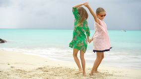 Little happy kids have a lot of fun at tropical beach playing together. Little girls having fun at tropical beach playing together at shallow water. Adorable stock footage