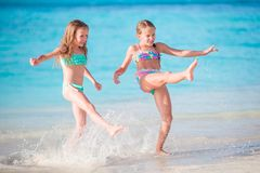 Little happy kids have a lot of fun at tropical beach playing together at shallow water. Royalty Free Stock Photos
