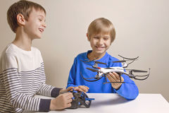 Little happy kids playing with the quadcopter drone at home. Technology, education, leisure, toys concept stock photo