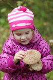 Little happy pretty girl in pink holds two mushrooms Stock Photos