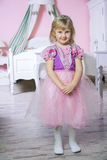 Little happy princess girl in pink dress and crown in her royal room posing and smiling. stock images