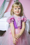 Little happy princess girl in pink dress and crown in her royal room posing and smiling. Stock Photos