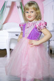Little happy princess girl in pink dress and crown in her royal room posing and smiling. Royalty Free Stock Photos