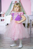 Little happy princess girl in pink dress and crown in her royal room posing and smiling. stock photo