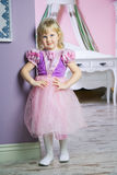 Little happy princess girl in pink dress and crown in her royal room posing and smiling. royalty free stock photography