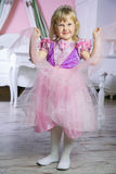 Little happy princess girl in pink dress and crown in her royal room posing and smiling. Royalty Free Stock Image