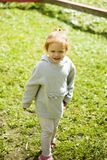 Little happy red-haired girl runs on cut green grass in a children park under the pleasant sun royalty free stock photo
