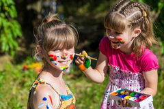 Little happy sisters play with colors in the park, children play, children paint each other Royalty Free Stock Images