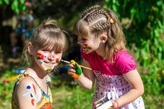 Little happy sisters play with colors in the park, children play, children paint each other. Art and painting concept stock photography