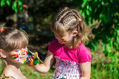 Little happy sisters play with colors in the park, children play, children paint each other Stock Photos