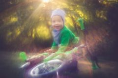 Little happy smiling boy kid near bike in sunny summer day stock images