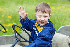 Little happy smiling boy waving his hand. On green background Stock Photos