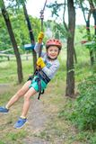A little happy and smiling rock climber tie a knot on a rope. A person is preparing for the ascent. The child learns to tie a knot. Checking the insurance for stock photography