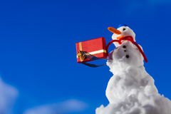 Little happy snowman with christmas gift box outdoor. Winter season. Stock Photos
