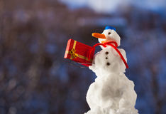 Little happy snowman with christmas gift box outdoor. Winter season. Stock Photo