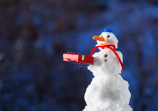Little happy snowman with christmas gift box outdoor. Winter season. Royalty Free Stock Images