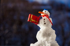 Little happy snowman with christmas gift box outdoor. Winter season. Stock Photography