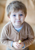 Little happy toddler boy eating lollipop Stock Photo