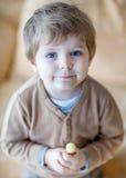 Little happy toddler boy eating lollipop. Indoor stock photo