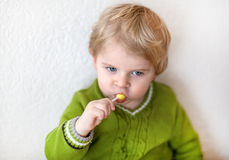 Little happy toddler boy eating lollipop. Little happy toddler boy one year old eating lollipop indoor Royalty Free Stock Photos