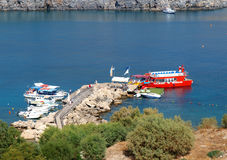 Little harbour. In Lindos, Greece. The boat service takes tourist to the most interesting spots along Rhodes island, Greece. Photograph taken on September, 2011 royalty free stock photo