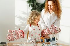 Little hard working child wears kitchen glove and apron, going to help her mother cook dinner, has happy expression stock image