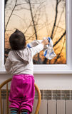 Little hardworking girl rubbing glass with cloth on window Stock Photography