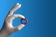 Little heart handled with care. Little red heard held by a hand with a medical white glove on blue background Royalty Free Stock Image