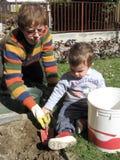 Little help gardener. A little baby boy helps his grandmother in garden works Royalty Free Stock Photos