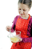 Little helper. An image of a little girl stirring something in a bowl stock photography