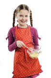 Little helper. An image of a little girl stirring something in a bowl royalty free stock photography
