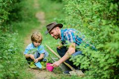 Little helper in garden. Farm family. Little boy and father in nature background. Gardening tools. Gardening hobby. Dad. Teaching little son care plants. Spring royalty free stock photography