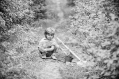 Little helper in garden. Planting flowers. Growing plants. Take care of plants. Boy with watering can. Small boy child. Love nature. Digging soil for green royalty free stock photography