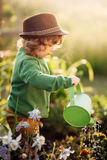 Little helper. The little girl with the watering can in the garden royalty free stock photography
