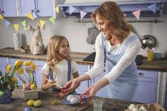 Cheerful mum and kid painting chicken eggs for holiday. Little helper. Happy mom and child standing in the cuisine and selecting rose color for holiday Royalty Free Stock Image