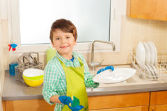 Little helper washing plates in the kitchen Stock Photos