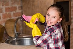 Little helper young girl wash dishes yellow gloves stock photography