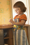 Little helping hands. Little girl, wearing apron, doing some housework in the kitchen Stock Photo