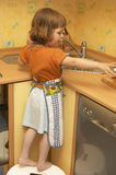 Little helping hands. Little girl, wearing apron, doing some housework in the kitchen Stock Photography
