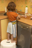 Little helping hands. Little girl, wearing apron, doing some housework in the kitchen Stock Photos