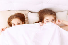 Little hilarious girls covered with blanket Stock Photo