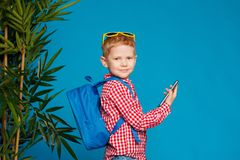 Little hipster boy with backpack and sunglasses holding telephone. Concept travel, education, technology. Isolated on the blue background Stock Image
