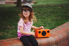 Little hipster girl listens music on wireless retro looking spea Royalty Free Stock Photo