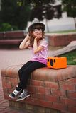 Little hipster girl listens music on wireless retro looking spea Royalty Free Stock Photography